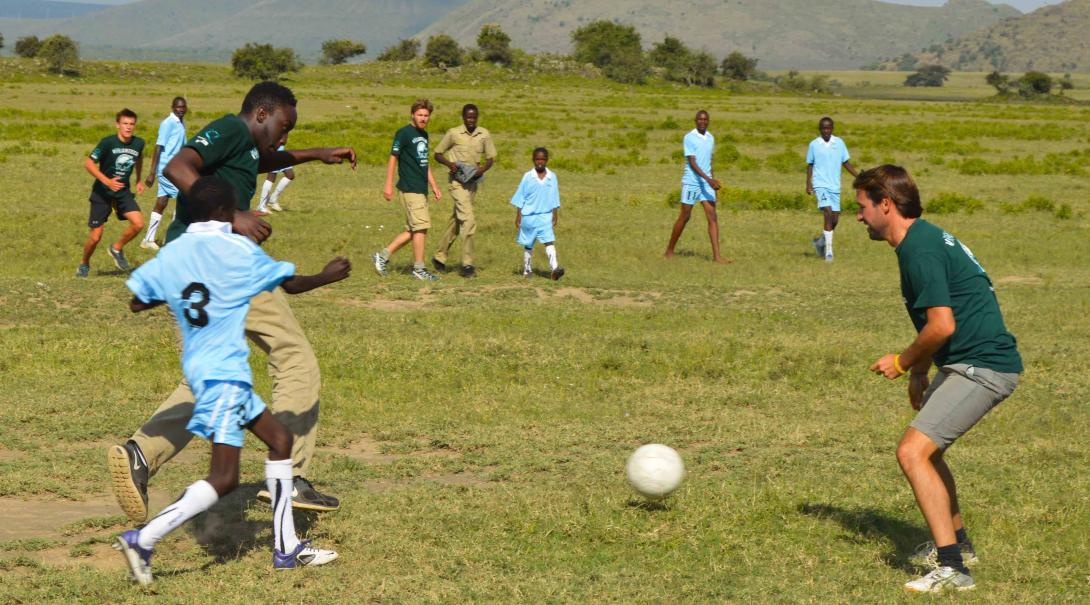 A group of Projects Abroad volunteers doing Sports Coaching internship play football with children in Kenya.